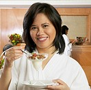 Asian woman in spa bathrobe eating cereal in glass