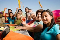 Large Hispanic family toasting at party outdoors