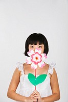 Asian woman holding flower in front of mouth