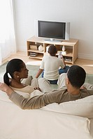 Rear view of African family watching television in livingroom