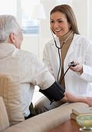 Hispanic female doctor taking patientÆs blood pressure