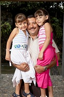 Hispanic father hugging daughters