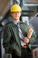 Businessman in hard hat carrying blueprints