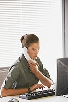 Businesswoman sitting at desk talking on telephone