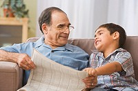 Hispanic grandfather and grandson reading newspaper on sofa