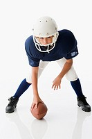 Studio shot of boy wearing football uniform