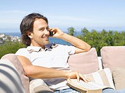 Man outdoors with book on cell phone