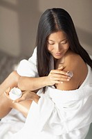 Asian woman applying lotion to shoulder