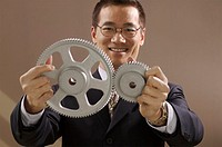 Asian businessman holding gear wheels