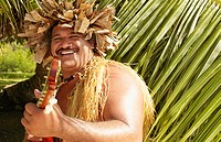 Pacific Islander man in traditional dress playing guitar