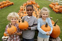 Portrait of children holding pumpkins