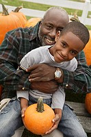 Portrait of African father and son holding pumpkin