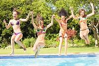 Four teenage girls jumping into pool