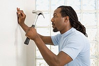 African man hammering nail into wall