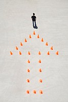 Traffic cones forming arrow with man at top