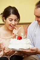 Hispanic man giving girlfriend birthday cake