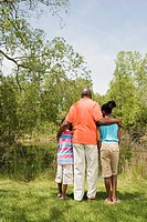Rear view of African grandfather and grandchildren hugging in park