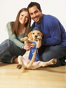 Multi-ethnic couple holding puppy dog and blue ribbon