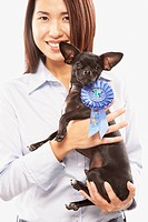 Portrait of Asian woman holding dog with blue ribbon