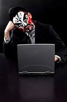 Businessman with oriental mask using laptop