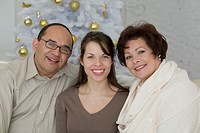 Hispanic parents and adult daughter next to Christmas tree
