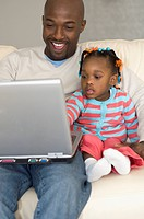 African father and daughter looking at laptop