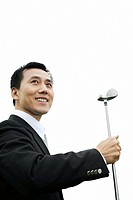 Businessman smiling while holding golf club