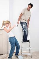 Woman avoiding paint from boyfriend´s paint brush