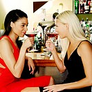 Two ladies enjoying cocktail in a pub