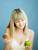 A young woman with a cupcake and green apple