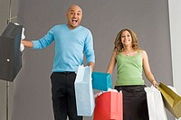 Couple jumping holding shopping bags