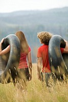 Young adult couple carrying inflatable rings in field