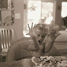 Young boy making face at table