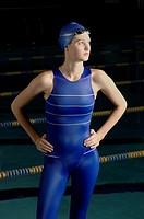Female swimmer standing by pool