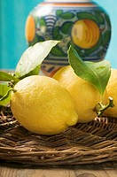 Fresh lemons with leaves on wicker tray