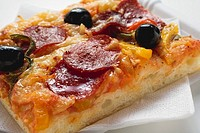 A slice of salami pizza with peppers and olives
