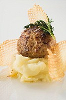A meatball on mashed potato