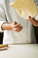 Shaping pizza dough throwing it in the air