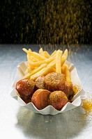 Sprinkling curry powder onto currywurst and chips