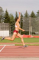 Side view of young adult woman on running track