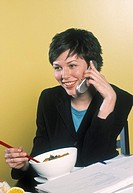 Businesswoman talking on cell phone and eating