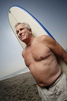 Mature man holding surfboard