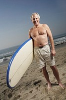 Mature man holding surfboard at the beach