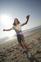 Mature woman with hula hoops on the beach