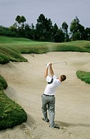 Man playing golf out of sand trap