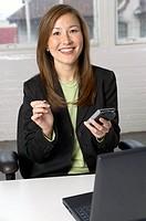 Asian businesswoman using electronic organizer