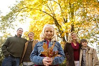 Girl holding autumn leaves with family