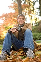 Low angle view of boy sitting in autumn leaves