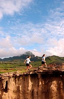 Young women running along cliff´s edge, Hawaii
