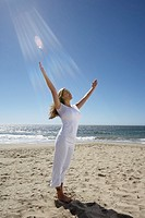 Young woman with arms raised at beach